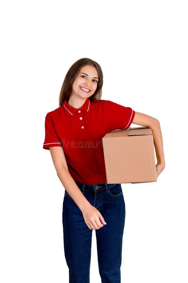 Szczęśliwa młoda doręczeniowa dziewczyna w czerwonej koszulce trzyma kartonu pakuneczka pudełko pod jej ręką odizolowywającą na b obraz stock