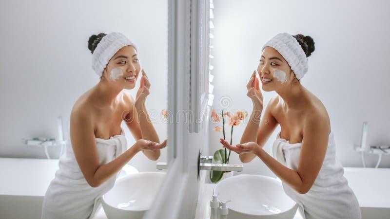 Szczęśliwa młoda kobieta stosuje śmietankę w łazience obrazy stock