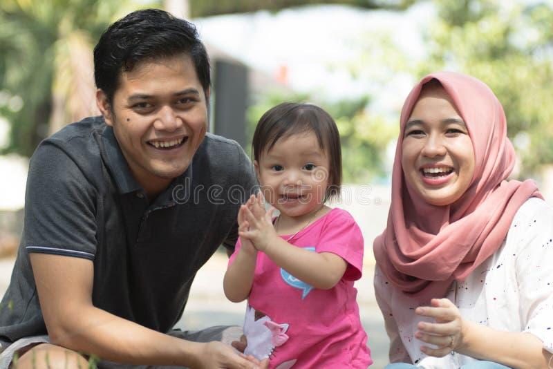 Szczęśliwa młoda muzułmańska rodzina z jeden dziećmi bawić się przy parkowym i patrzeje kamera w słonecznym dniu fotografia stock