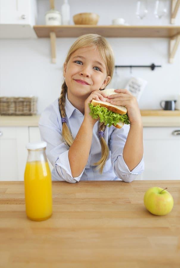 Szczęśliwa mała dziewczynka cieszy się i pije soku pomarańczowego obsiadanie przy jaskrawym szkolny wiek zdrową śniadaniową łasow obraz stock