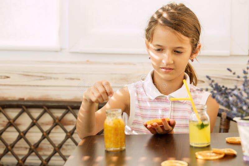 Szczęśliwa mała dziewczynka cieszy się i pije soku pomarańczowego obsiadanie przy jaskrawym szkolny wiek zdrową śniadaniową łasow obraz royalty free
