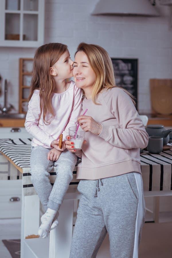 Szczęśliwa mała dziewczynka i jej piękna potomstwo matka śniadanie wpólnie w białej kuchni Córka całuje jej mamy macierzyński obrazy stock