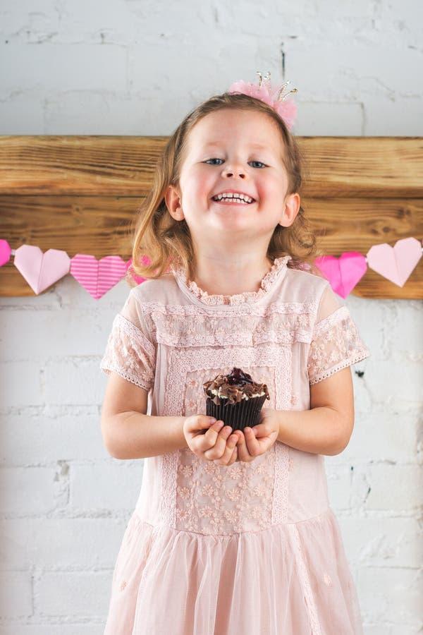 Szczęśliwa małej dziewczynki mienia babeczka zdjęcie royalty free