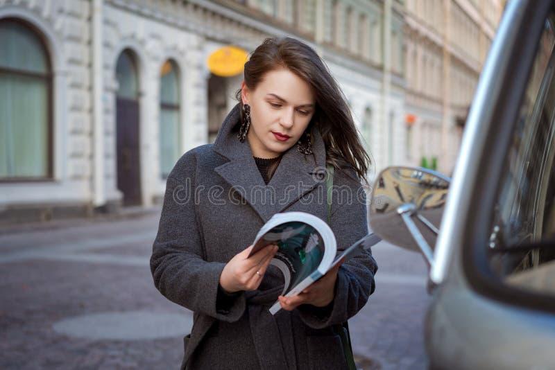 Szczęśliwa mody kobieta czyta magazyn na miasto ulicie zdjęcia stock