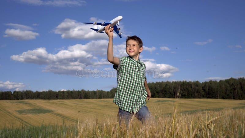 Szczęśliwa nastoletnia chłopiec bawić się z zabawkarskim samolotem przeciw pięknemu natury tłu, zabawę fotografia royalty free