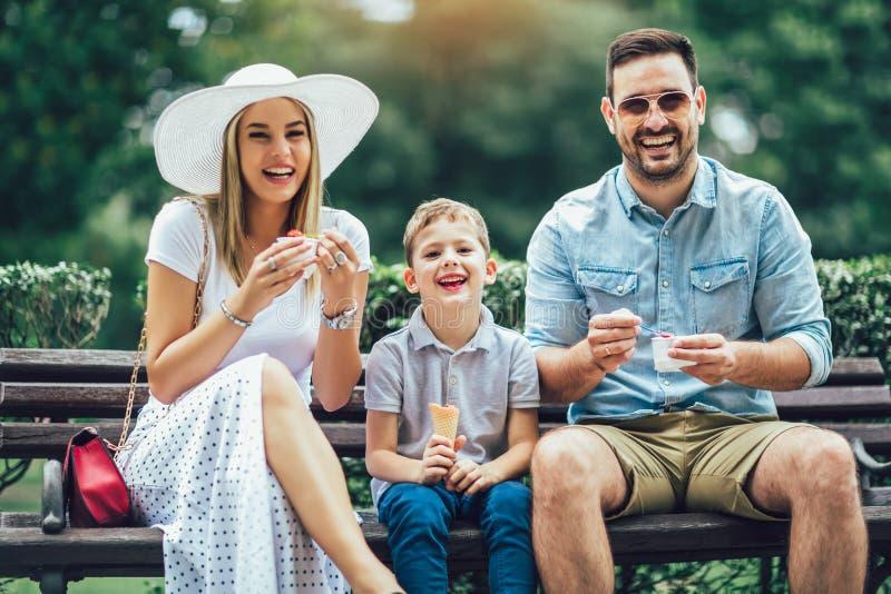 Szczęśliwa rodzina wydaje ich weekend w parku Jedzą lody zdjęcie stock
