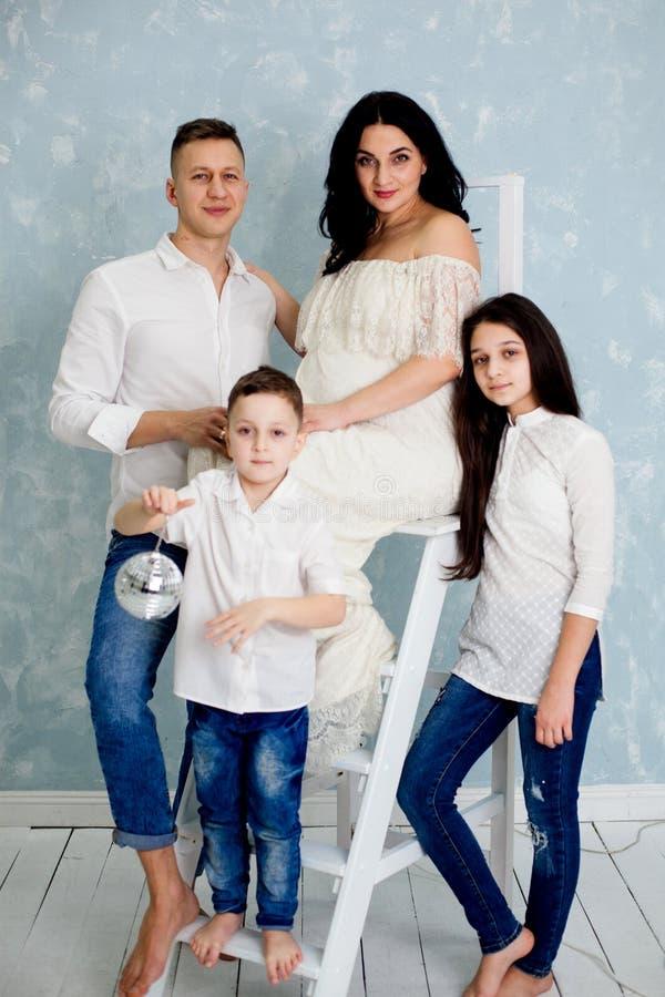 Szczęśliwa rodzina z kobietą w ciąży i dziećmi pozuje w studiu fotografia royalty free