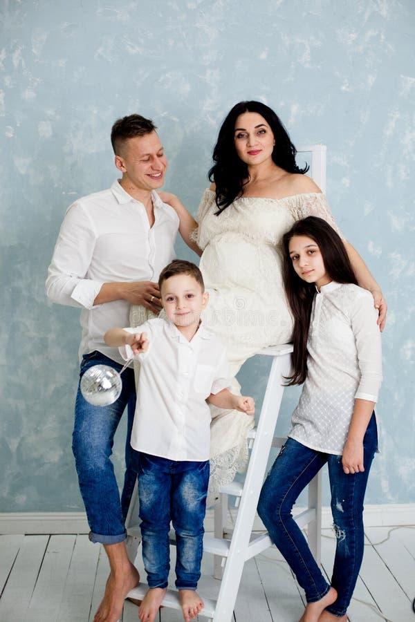 Szczęśliwa rodzina z kobietą w ciąży i dziećmi pozuje w studiu obraz royalty free