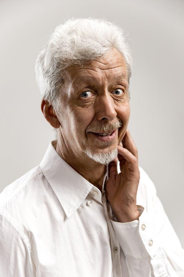 Szczęśliwa starsza biznesowego mężczyzny pozycja i ono uśmiecha się przeciw szaremu tłu zdjęcie stock