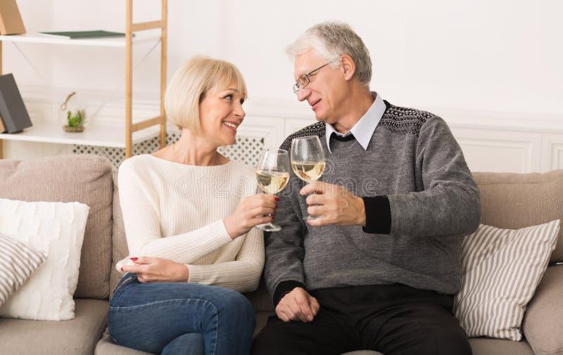 Szczęśliwa starsza para pije wino, świętuje ślubną rocznicę zdjęcia stock