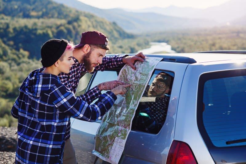 Szczęśliwa turystyczna para z papierową mapą blisko samochodu Uśmiechnięci młodzi ludzie używa mapę Podróżować dzierżawiącym samo zdjęcia stock