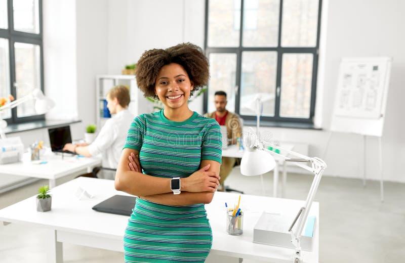 Szczęśliwa uśmiechnięta amerykanin afrykańskiego pochodzenia kobieta przy biurem fotografia stock