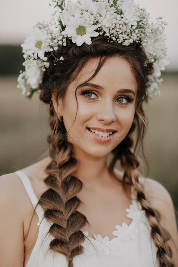 Szczęśliwa uśmiechnięta dziewczyna z warkoczami i kwiecisty wianek w biel sukni w boho projektujemy w lecie outdoors obrazy stock