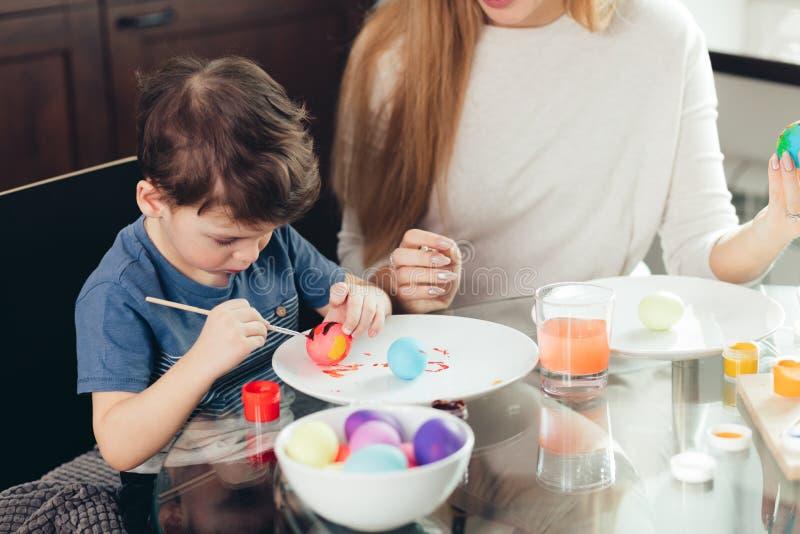 Szczęśliwa Wielkanocna potomstwo matka i jej mały syn maluje Wielkanocnych jajka obrazy royalty free