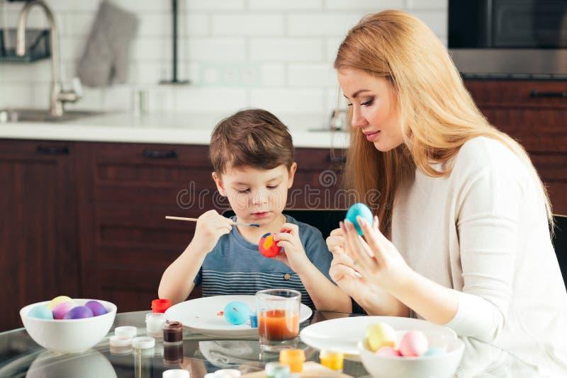 Szczęśliwa Wielkanocna potomstwo matka i jej mały syn maluje Wielkanocnych jajka zdjęcia stock