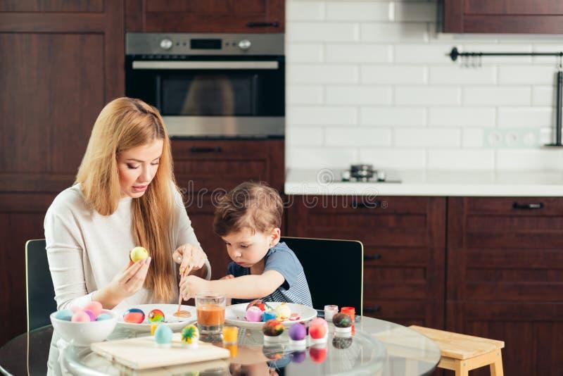 Szczęśliwa Wielkanocna potomstwo matka i jej mały syn maluje Wielkanocnych jajka fotografia royalty free