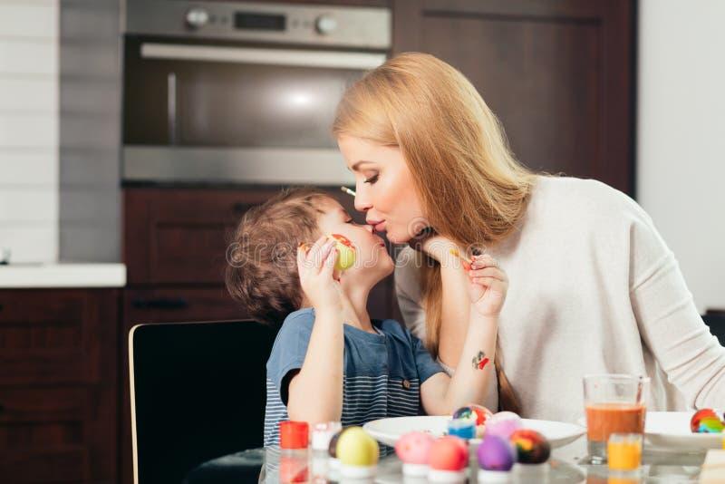 Szczęśliwa Wielkanocna potomstwo matka i jej mały syn maluje Wielkanocnych jajka zdjęcie stock