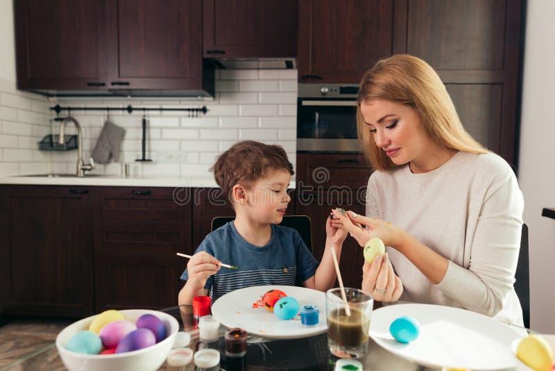Szczęśliwa Wielkanocna potomstwo matka i jej mały syn maluje Wielkanocnych jajka zdjęcie royalty free