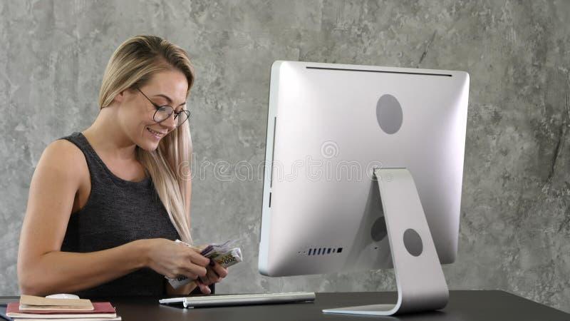 Szczęśliwego z podnieceniem pomyślnego młodego biznesowej kobiety mienia pieniądze dolarowi rachunki i patrzeć gotówkowego odczuc zdjęcia stock