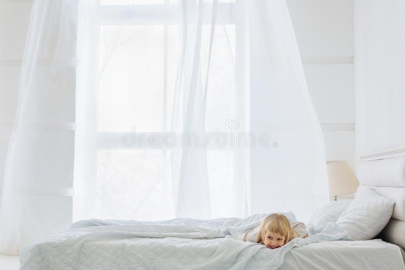 Szczęśliwej dziewczyny łgarski puszek na łóżku w białym pokoju z okno fotografia stock