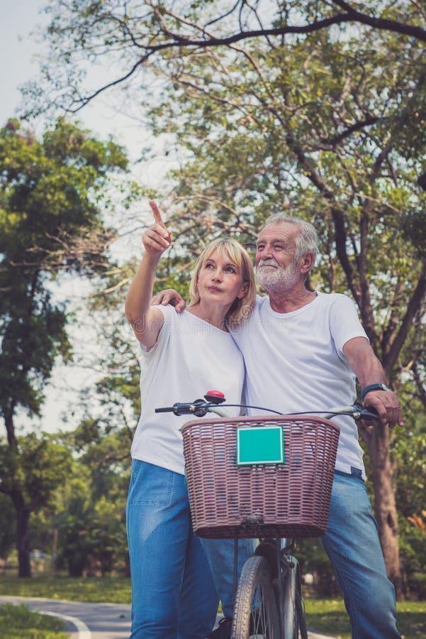 Szczęśliwej starszej pary jeździeccy bicykle przy jesień parkiem fotografia stock