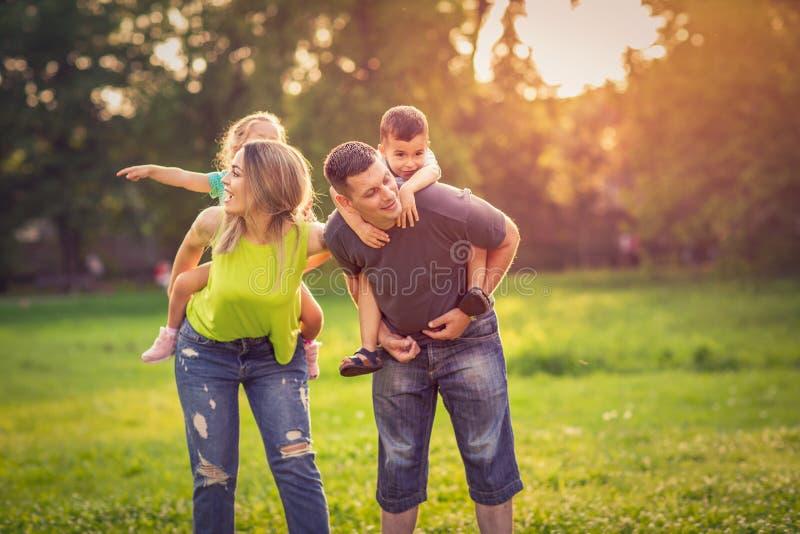 Szczęśliwi śmieszni rodzice daje dzieci piggyback przejażdżkę w parku obraz stock