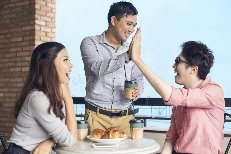 Szczęśliwi coworkers na kawowej przerwie w kawiarni fotografia royalty free