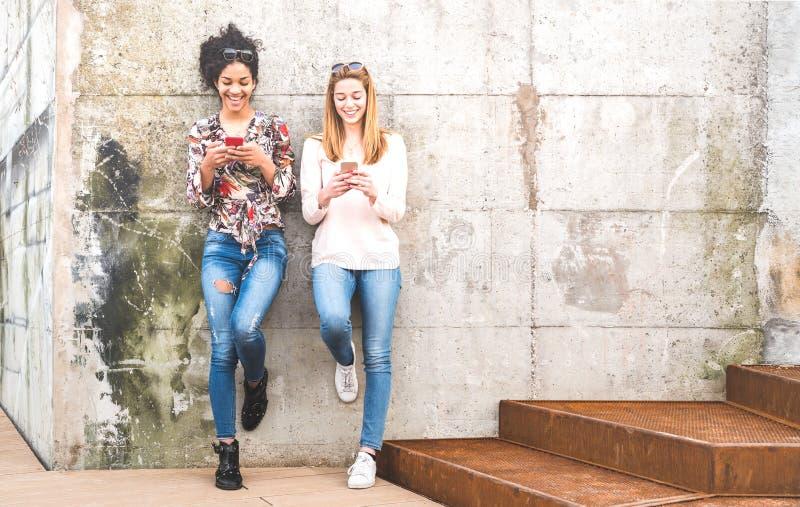 Szczęśliwi dziewczyna najlepszy przyjaciele ma zabawę z mobilnym mądrze telefonem outdoors - przyjaźni pojęcie z millenial dziewc fotografia royalty free