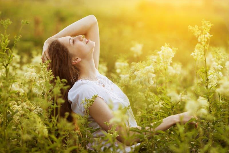 Szczęśliwi piękni dziewczyna stojaki wśród wildflowers zdjęcia royalty free