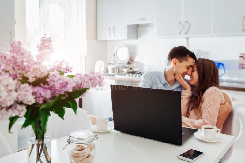 Szczęśliwi potomstwa dobierają się używać laptop podczas gdy mieć śniadanie w nowożytnej kuchni Młodego człowieka i kobiety napoj zdjęcie stock