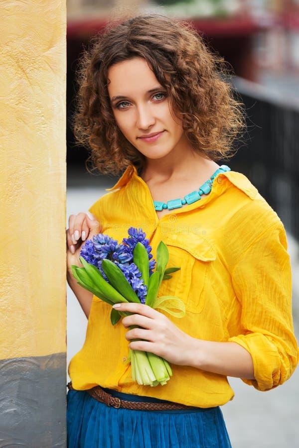 Szczęśliwi potomstwa fasonują kobiety w żółtej koszula z bukietem kwiaty obraz royalty free
