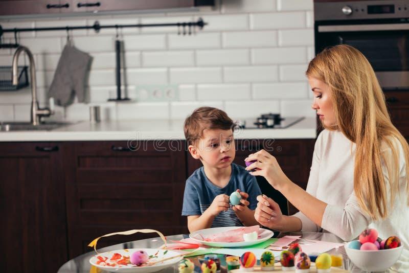 Szczęśliwi potomstwa matka i syn je wpólnie domowej roboty Wielkanocnych jajka fotografia stock