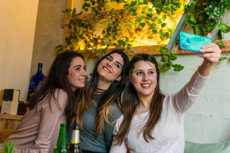 Szczęśliwi przyjaciele grupowi pijący piwnego i bierze selfie przy browaru baru restauracją obrazy stock