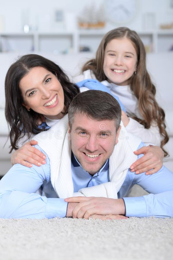 Szczęśliwi rodzice i córka pozuje w pokoju obraz stock