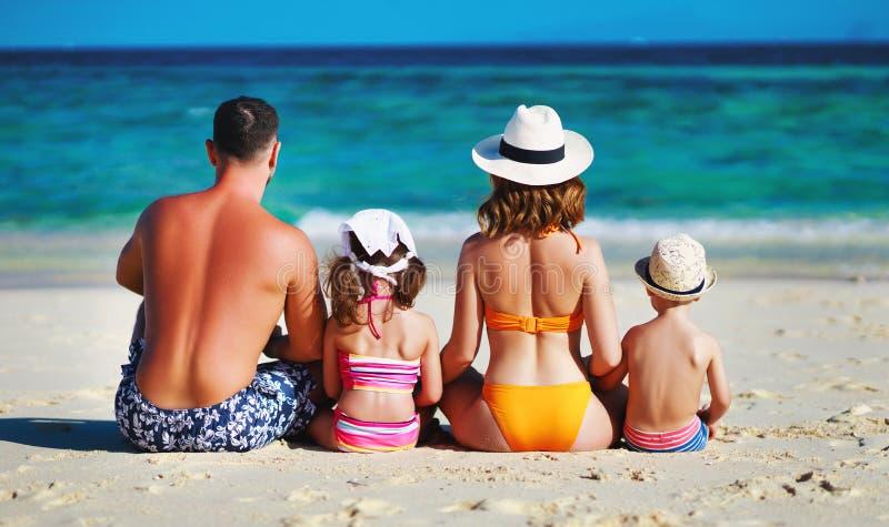 Szczęśliwi rodzinni ojca, matki i dzieci plecy na plaży przy morzem, obraz stock