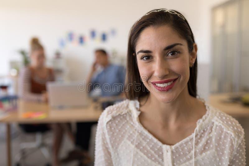 Szczęśliwy żeński wykonawczy ono uśmiecha się w biurze zdjęcie royalty free