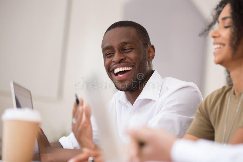 Szczęśliwy afrykański biznesmen śmia się opowiadający pracować wraz z życzliwymi kolegami obrazy stock