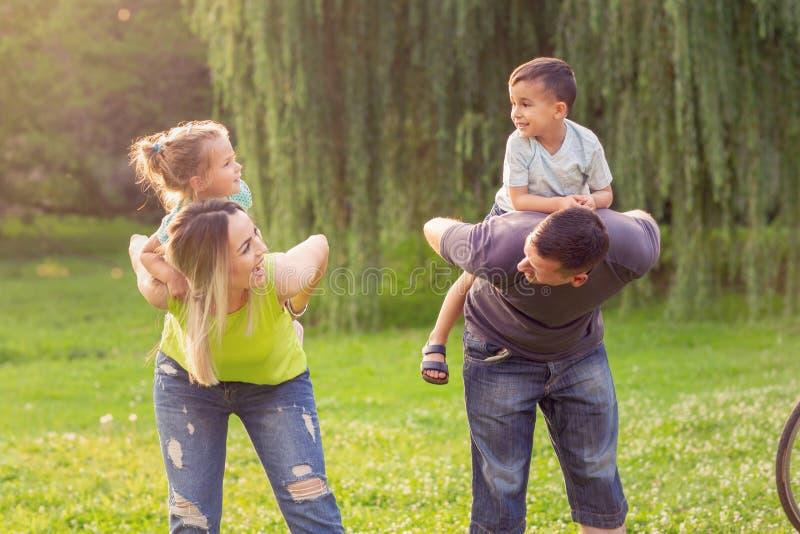 Szczęśliwy dzieciństwo - rodzice daje piggyback przejażdżce dzieci zdjęcia royalty free