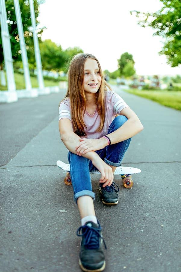 Szczęśliwy dziewczyna nastolatka 8-12 lat, siedzi na deskorolka W lecie w mieście odpoczywa dalej po szkolnych lekcji fotografia royalty free