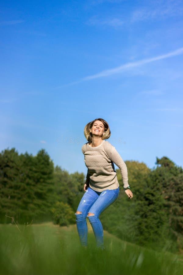 Szczęśliwy młodej kobiety doskakiwania, nieba i drzewa tło, zdjęcia stock