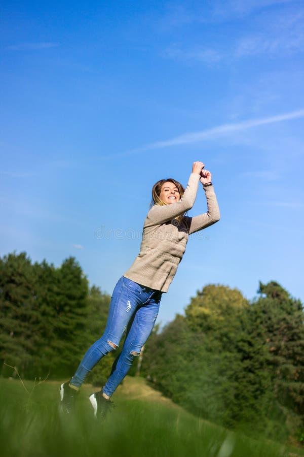 Szczęśliwy młodej kobiety doskakiwania, nieba i drzewa tło, fotografia stock