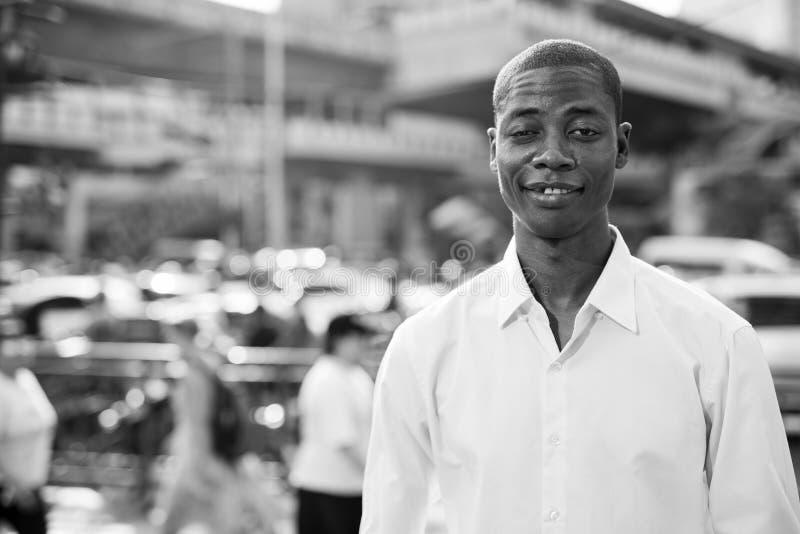 Szczęśliwy młody łysy Afrykański biznesmen w miasto ulicach w czarny i biały zdjęcie stock