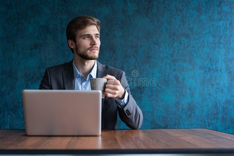 Szczęśliwy młody biznesmen używa laptop przy jego biurowym biurkiem obraz stock