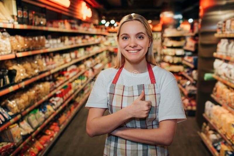 Szczęśliwy pozytywny młoda kobieta stojak w linii w sklepie spożywczym Patrzeje na kamerze i uśmiechu Wzorcowego utrzymania duży  obrazy royalty free