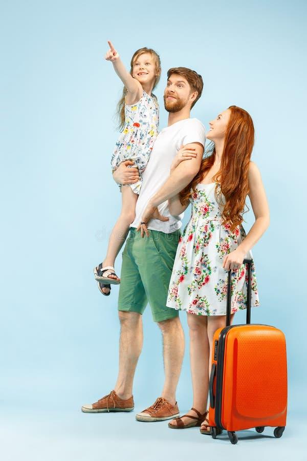 Szczęśliwy rodzic z córką i walizką przy studiiem na błękitnym tle zdjęcia royalty free