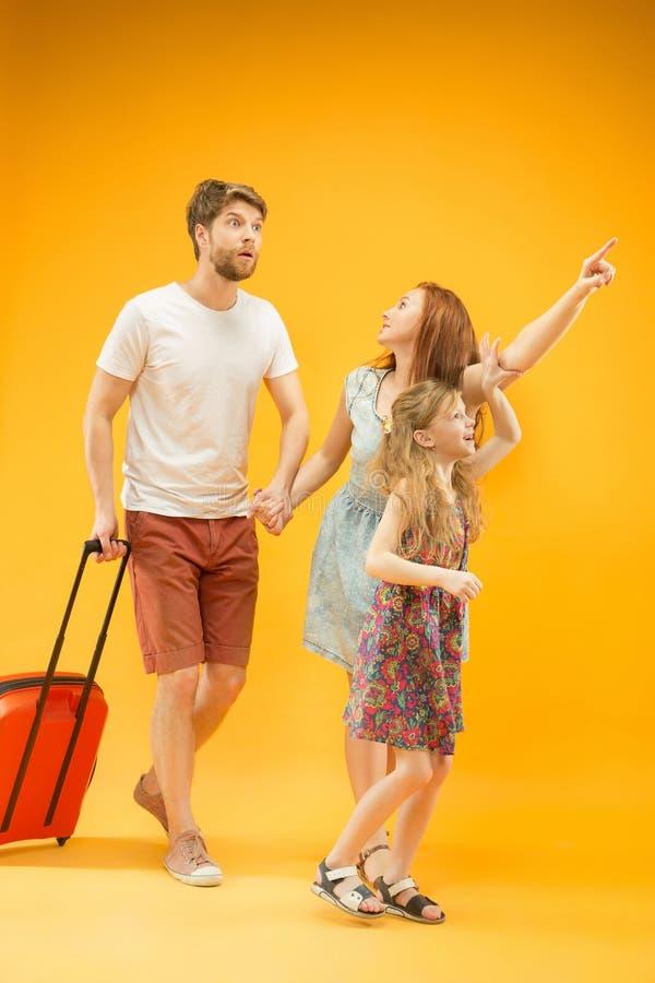 Szczęśliwy rodzic z córką i walizką przy studiiem odizolowywającym na żółtym tle obrazy stock