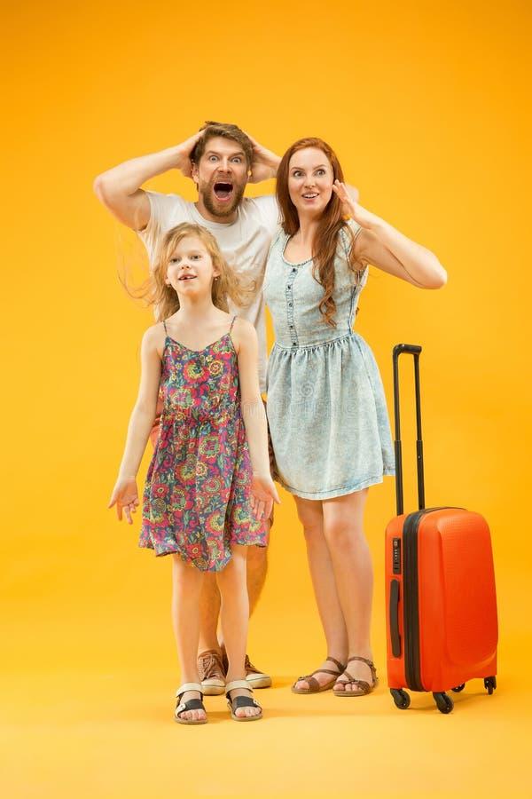 Szczęśliwy rodzic z córką i walizką przy studiiem odizolowywającym na żółtym tle zdjęcie stock