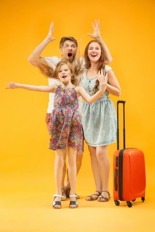 Szczęśliwy rodzic z córką i walizką przy studiiem odizolowywającym na żółtym tle zdjęcia stock