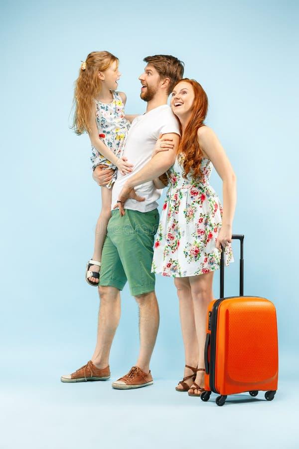Szczęśliwy rodzic z córką i walizką przy studiiem odizolowywającym na błękitnym tle fotografia stock
