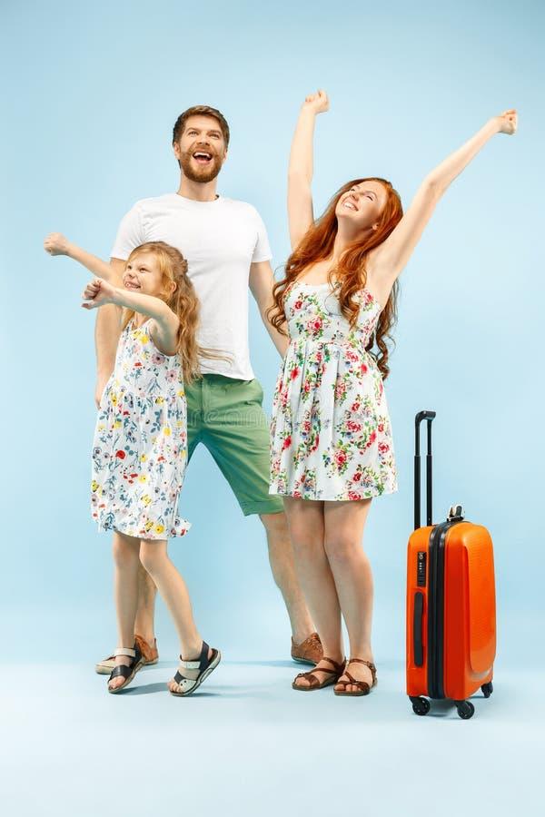 Szczęśliwy rodzic z córką i walizką przy studiiem odizolowywającym na błękitnym tle zdjęcie royalty free